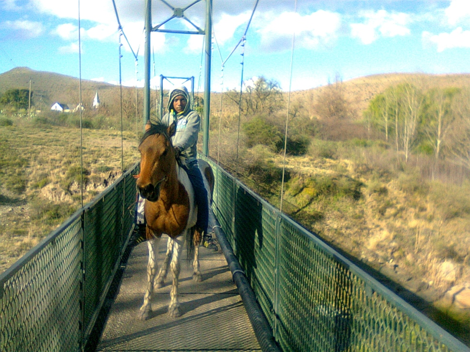 Nieu Bethesda-boy on horse on footbridge